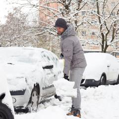 Man shoveling her parking lot after a winter snowstorm.