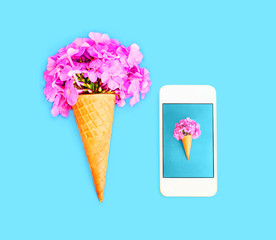 Ice cream cone with flowers and smartphone over blue colorful background top view