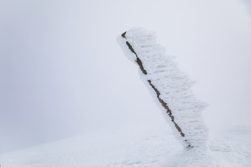 Trekking sign pole on summit covered by heavy snow.