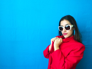 Fashion sexy fierce model in white sunglasses, beautiful young woman with hands in her red winter coat with long brunette hair and vintage retro and colorful clothes in bright vibrant blue background