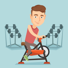 Young man riding stationary bicycle.