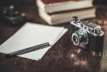 Retro camera and sheets of paper on table. Writing a story.