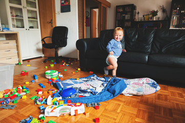 Adorable 1 year old baby boy with funny facial expression playing in a very messy living room