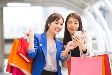 Happy shopping asia woman use smartphone with friends at the background.