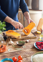 Man cooking healthy food of squash on wooden table
