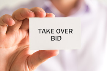 Businessman holding a card with TAKE OVER BID message