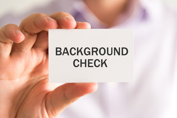 Businessman holding a card with BACKGROUND CHECK message