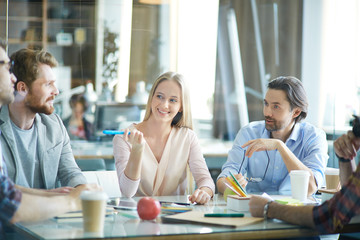 Group of creative businesspeople, three men and blond woman, sitting at meeting round table in light modern office space, all gesturing actively and discussing latest project