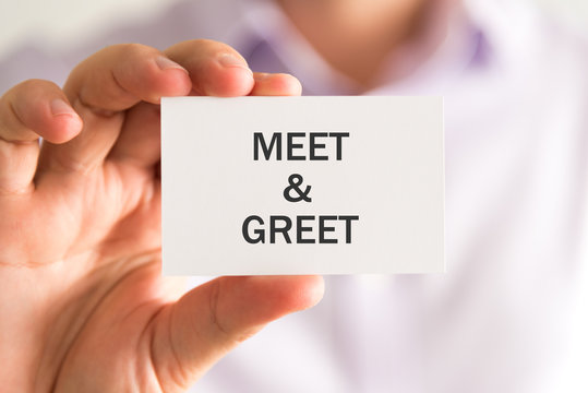 Businessman holding a card with MEET AND GREET message