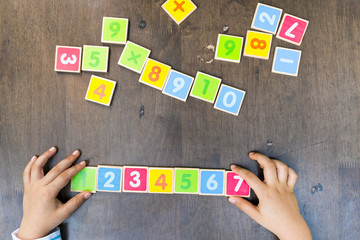 Child Hands With Wooden Toy Plate Numbers On Wood Table.