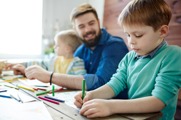 Two little boys having art class: they concentrated on work while their bearded male teacher looking at them with toothy smile