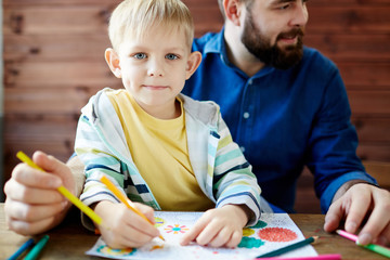 Cute little blond-haired boy with deep grey eyes sitting on laps of his bearded father, looking at camera and holding pencil in hand for coloring picture