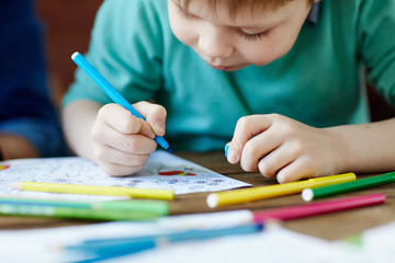 Creative little boy bending head over illustration and coloring it with felt-tip pens, close-up shot