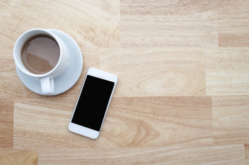 coffee and smartphone on wooden table and copy space, soft focus