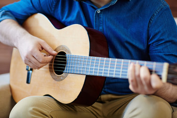 Close-up shot of man sitting on comfortable armchair and practicing in playing acoustic guitar