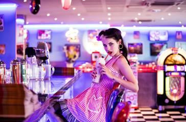 Portrait d'une jeune Pin'Up de profil, buvant délicatement un milkshake