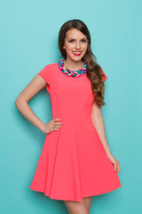 Smiling Woman In Pink Dress And Colorful Braided Necklace