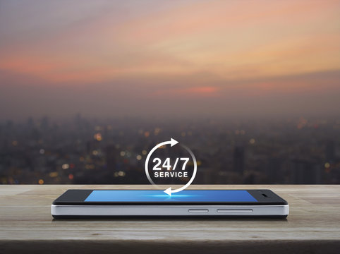 24 hours service icon on modern smart phone screen on wooden table over blur of cityscape on warm light sundown, Full time service concept