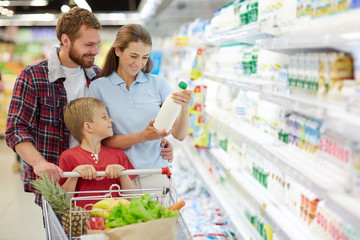 Attractive young woman in casualwear with milk bottle in hands searching expiration date while her husband holding her around waist