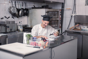 happy smiling young chef writing ordering kitchen