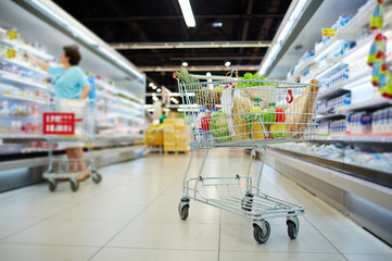 Shopping cart full of grocery standing next to shelves with dairy products in hypermarket