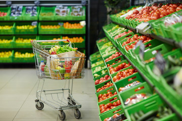 Metal shopping trolley with healthy grocery items standing in fruit and vegetable department of hypermarket