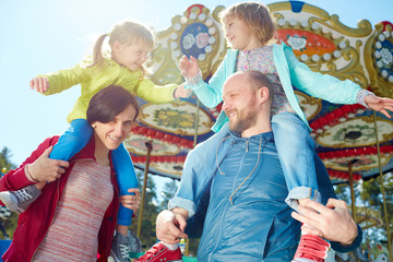 Carefree little girls playing with each other while sitting on shoulders of their smiling middle-aged parents, colorful merry-go-round observed on background