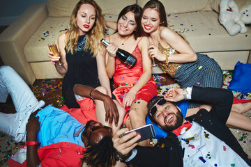 Middle-aged Asian man in sunglasses lying on floor covered with confetti and taking selfie with his beautiful female friends