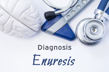 Diagnosis of Enuresis. Anatomical brain figure, neurological hammer and stethoscope lying on sheet of paper or book with the title neurological diagnosis of Enuresis. Concept for neurology