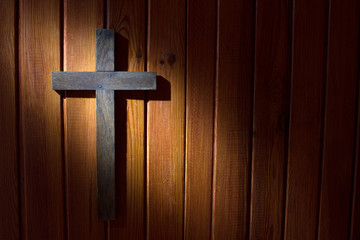 Cross on the wooden wall in night abstract easter background