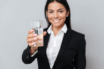 Smiling attractive business woman holding glass of mineral water