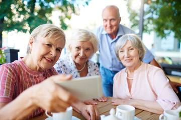 Cheerful seniors gathered together at wooden table for tea party and taking selfie with smartphone