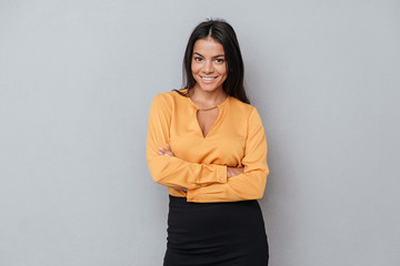 Woman standing with hands folded and looking at camera