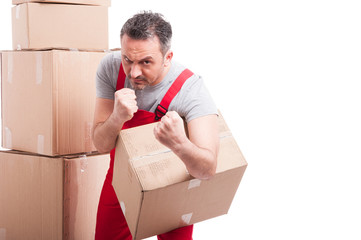 Mover guy holding cardboard box standing in fighting position