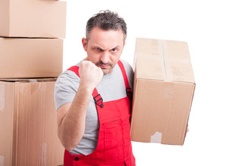 Mover guy holding cardboard box showing fist looking angry