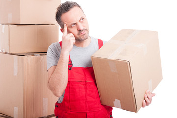 Mover guy holding cardboard box making thinking gesture