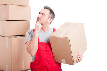 Mover man holding cardboard box making thinking gesture