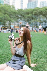 Young American Girl Using a Vintage Camera in Briant Park . Manhattan New York City US