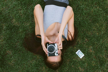 Young Girl Lying on the Grass Taking Pictures With a Vintage Camera