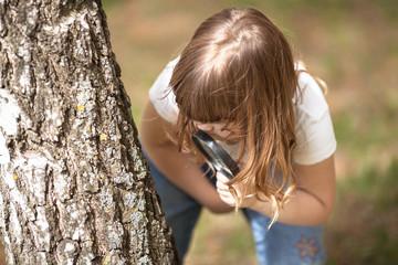 Kid girl explores bark of tree magnifying glass