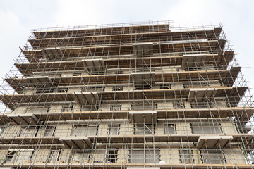 scaffolding on building site of new apartment building and sky