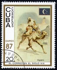 UKRAINE - CIRCA 2017: A stamp printed in Cuba, shows a man with a cargo moved on a camel Egypt, the series The mail in the nineteenth century, circa 1987