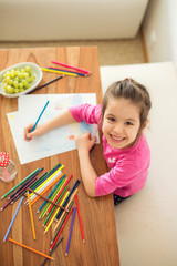 Cute little girl, drawing picture with pencils at home