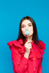 Young woman covering her face with lollipop over blue background. Wearing in shirt and jeans. Looking at camera