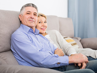 middle-aged married couple in house are warmly reconciled after quarrel