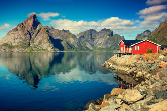 Beautiful fishing village on fjord. Beautiful nature with blue sky, reflection in water, rocky beach and fishing house (rorby). Lofoten, Reine, Norway