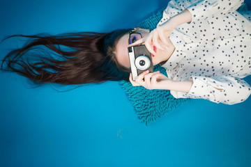 Cheerful girl lying on the floor with her camera in hands
