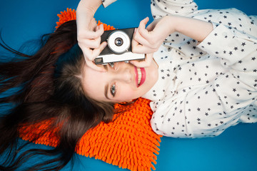 Girl with retro camera. Cheerful girl lying on the floor with her camera in hands