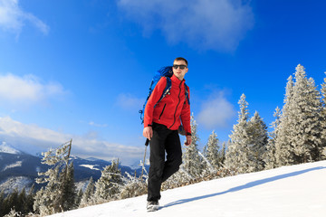 Hiker in winter mountains. Man with backpack trekking in mountains. Winter hiking