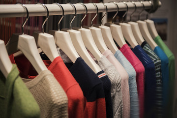 Color sweaters on a rack in a boutique store